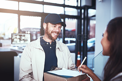 Buy stock photo Shot of a cheerful delivery man handing over a package to a customer and letting them sign on a digital tablet inside a building