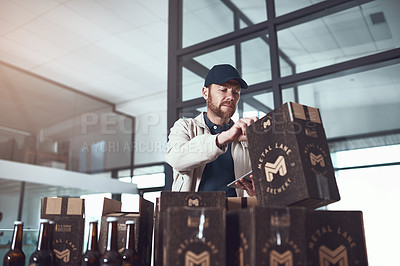 Buy stock photo Shot of a cheerful young man packing boxes on top of each other inside of a office building during the day