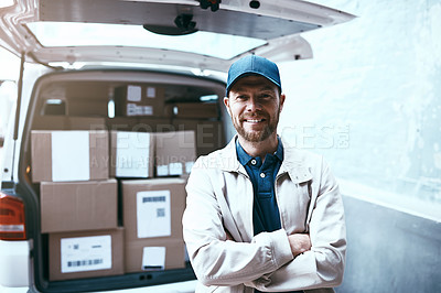 Buy stock photo Portrait of a cheerful young delivery man standing next to a van full of boxes with his arms folded outside during the day