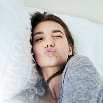 Buy stock photo Portrait of an attractive young woman blowing a kiss while lying in bed at home during the day