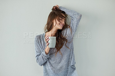 Buy stock photo Studio shot of an attractive young woman with her arm raised while drinking coffee against a white background