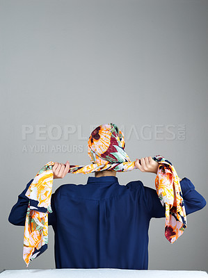 Buy stock photo Rearview studio shot of  an unrecognizable woman wearing a head scarf and tying it up while standing against a grey background