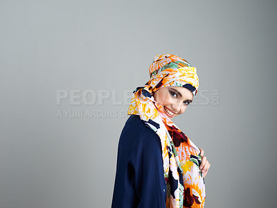 Buy stock photo Studio portrait of a confident young woman wearing a colorful head scarf while posing against a grey background