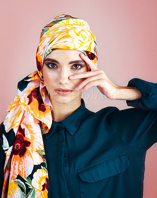 Buy stock photo Studio portrait of a confident young woman wearing a colorful head scarf while posing against a pink background