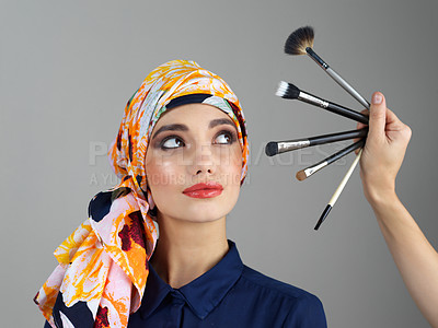Buy stock photo Studio shot of a confident young woman wearing a colorful head scarf while looking at different makeup brushes being held in front of her
