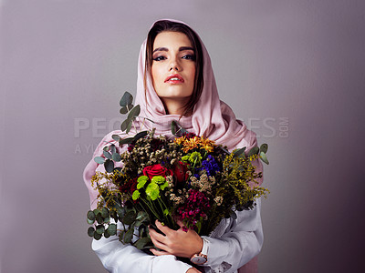 Buy stock photo Studio portrait of a confident young woman wearing a colorful head scarf and holding a bouquet of flowers against a grey background