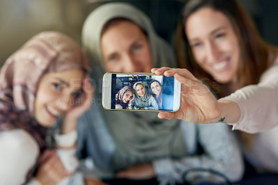 Buy stock photo Shot of a group of women taking selfies with a mobile phone in a cafe