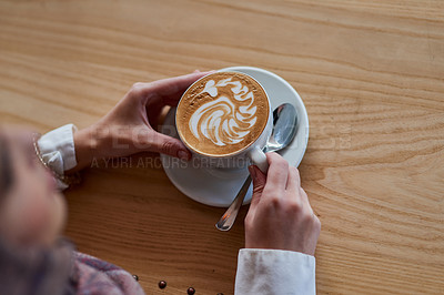 Buy stock photo High angle shot of a woman holding a cup of coffee decorated with froth art