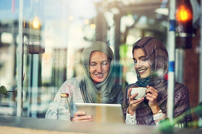 Buy stock photo Shot of two women using a digital tablet together in a cafe