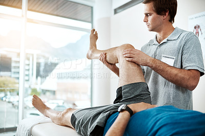 Buy stock photo Shot of a young male physiotherapist helping a client with leg exercises who's lying on a bed