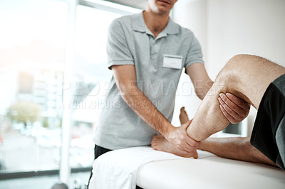 Buy stock photo Shot of an unrecognizable male physiotherapist helping a client with leg exercises who's lying on a bed