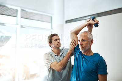 Buy stock photo Shot of a young male physiotherapist helping a client with stretching exercises in his office during the day