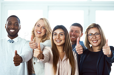 Buy stock photo Portrait of a group of confident work colleagues standing together while showing thumbs up against a white background