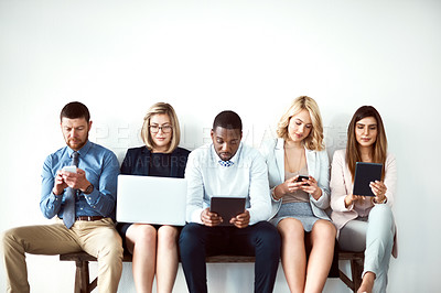 Buy stock photo Shot of a group of work colleagues seated next to each other while using electronic devices against a white background