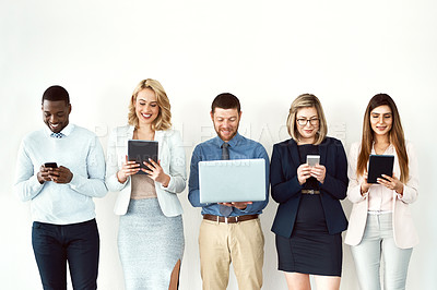 Buy stock photo Shot of a group of work colleagues standing next to each other while using electronic devices against a white background