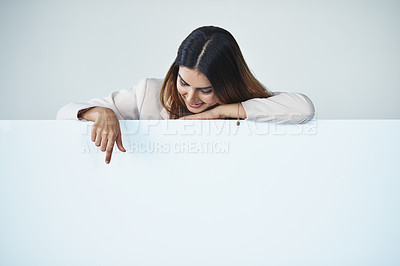 Buy stock photo Studio shot of an attractive young businesswoman pointing at copy space on a blank placard