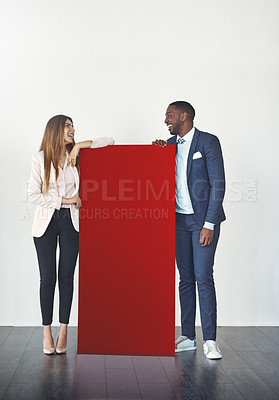 Buy stock photo Studio shot of a young businessman and businesswoman standing next to a blank red placard