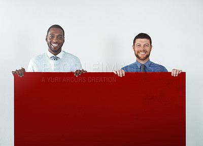 Buy stock photo Studio shot of two businessmen holding up a blank red placard
