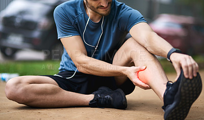 Buy stock photo Shot of a sporty young man holding his calf in pain while exercising outdoors