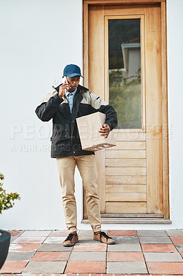 Buy stock photo Shot of a courier talking on a cellphone while making a delivery