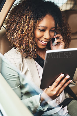 Buy stock photo Shot of an attractive businesswoman on a call and using a tablet during her morning commute
