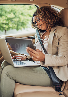 Buy stock photo Shot of an attractive businesswoman on a call while using a tablet and laptop during her morning commute
