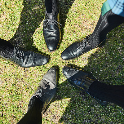 Buy stock photo Shot of a group of unrecognizable men's formal dress shoes standing next to each other in a circle outside during the day