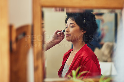 Buy stock photo Shot of a relaxed young woman's reflection in a mirror who's seated on a chair while getting her makeup done before a wedding