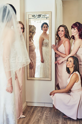 Buy stock photo Shot of a confident young bride looking at her reflection in a mirror while her bride's mades look a her