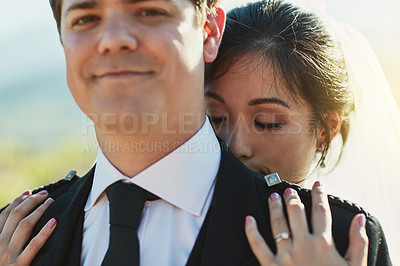 Buy stock photo Shot of a peaceful young bride holding his husband from behind with her eyes closed outside during the day
