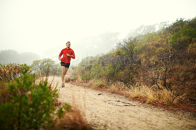Buy stock photo Shot of a sporty young man out for a trail run in the mountains