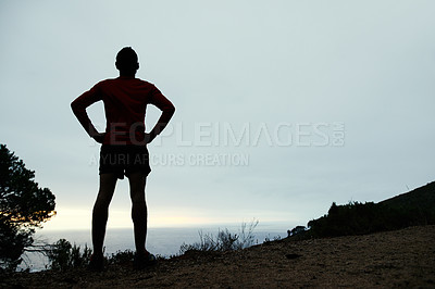 Buy stock photo Rearview shot of a man admiring the view while out for a run