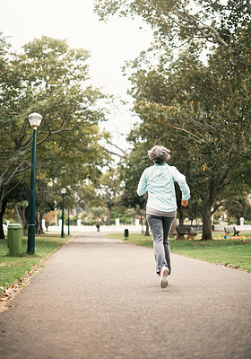 Buy stock photo Rearview shot of a senior woman out for a run in the park