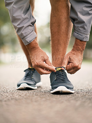 Buy stock photo Cropped shot of a man tying his shoelaces while out for a run in the park