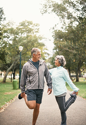 Buy stock photo Shot of a senior couple stretching before a run in the park