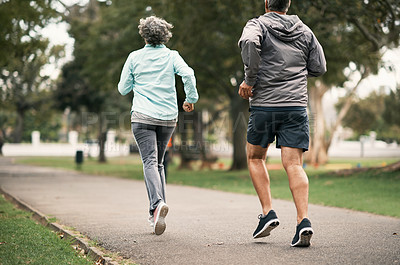Buy stock photo Rearview shot of a senior couple out for a run in the park