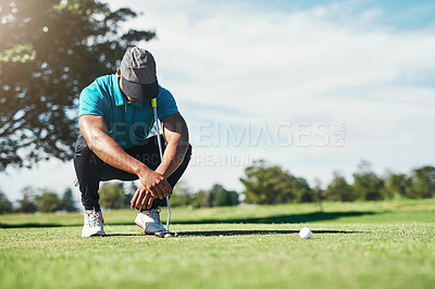 Buy stock photo Shot of a focused young male golfer looking at the ground while being seated on the grass outside during the day