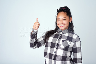 Buy stock photo Studio portrait of a cute young girl giving thumbs up against a gray background