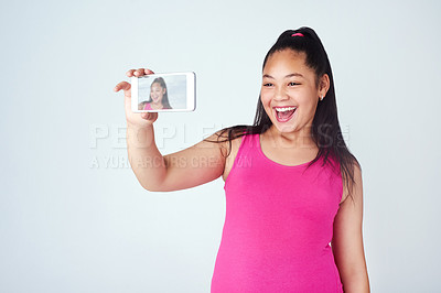 Buy stock photo Studio shot of a cute young girl taking a selfie with a mobile phone against a gray background