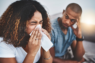 Buy stock photo Shot of a young woman blowing her nose with her boyfriend looking irritated in the background