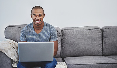 Buy stock photo Portrait of a handsome young man using a laptop at home