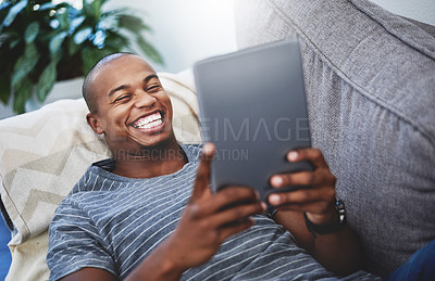 Buy stock photo Shot of a handsome young man using a digital tablet at home