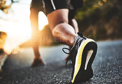 Buy stock photo Low angle shot of a man out exercising on a tarmac road