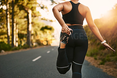 Buy stock photo Rearview shot of a young woman stretching before her run