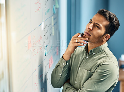 Buy stock photo Shot of a focused young businessman standing next to a white board while looking at it and contemplating inside of the office