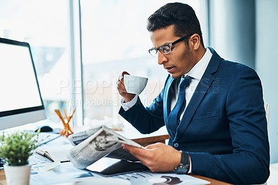 Buy stock photo Shot of a focused young businessman seated at his desk  while drinking coffee and reading a newspaper in the office