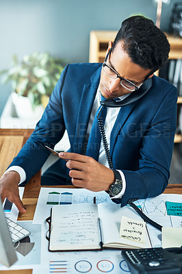 Buy stock photo Shot of a focused young businessman seated at his desk while taking on the phone and typing on a keyboard in the office