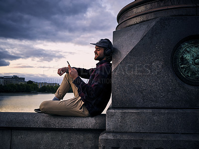 Buy stock photo Shot of a young man listening to music on his cellphone outside