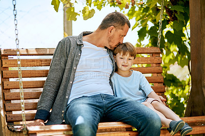 Buy stock photo Shot of a father and his adorable son relaxing together on a garden swing