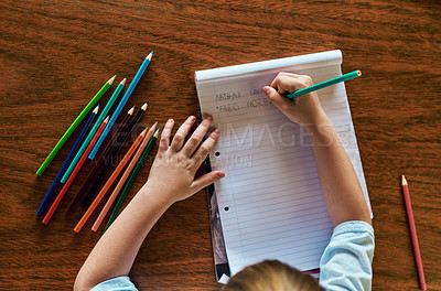 Buy stock photo High angle shot of a little boy sitting at a desk and writing on a notepad